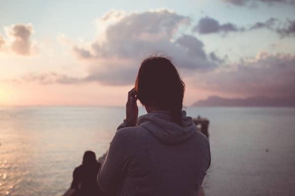 夕日を見つめる女性の後ろ姿